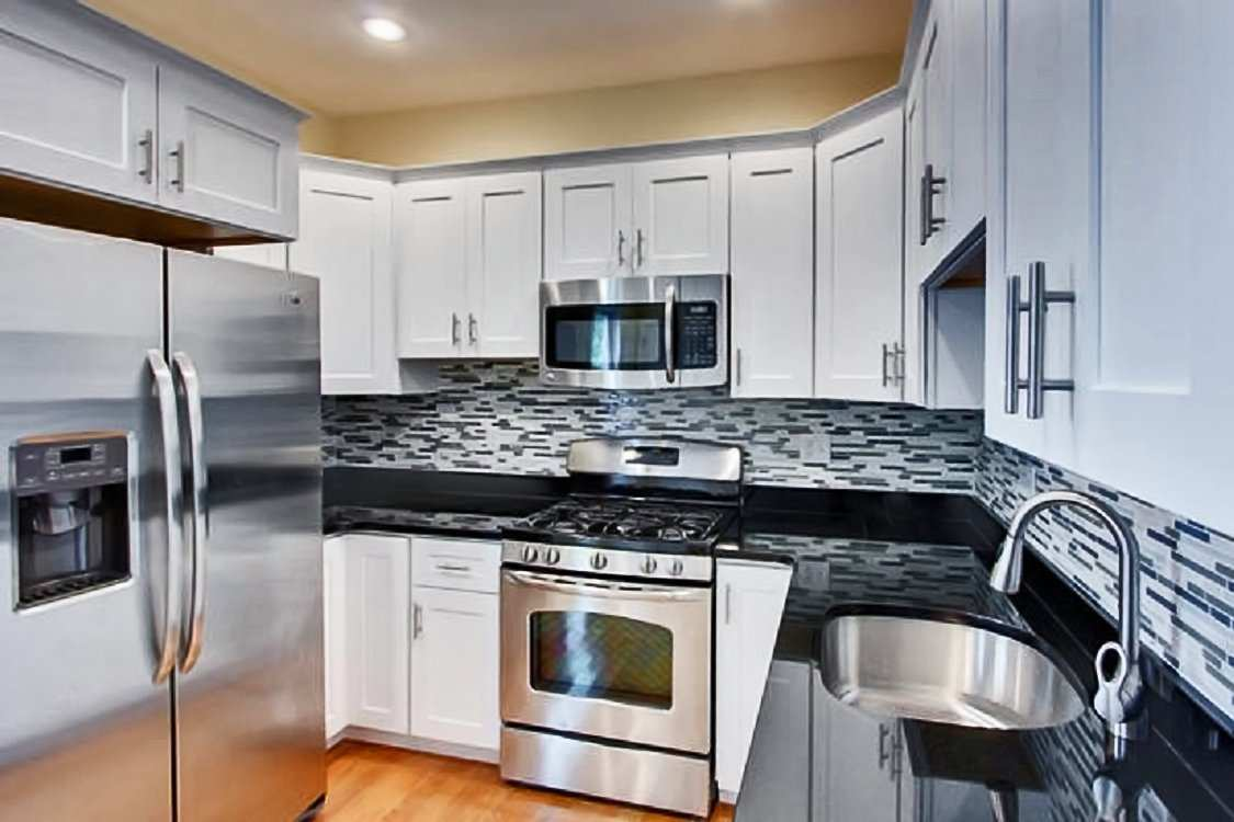 Kitchen Cabinet designs with white cabinets, built in appliances, and quartz countertops