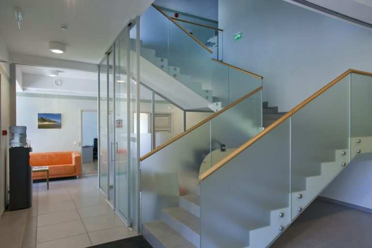A traditional house with a modern glass extension, two stories, with glass walls and a glass stairway railing