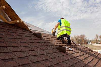 Columbus, Ohio roofing company roofer using air nailer installing asphalt roofing shingles