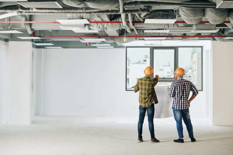 Construction engineers with blueprint in front of new window installation on wall