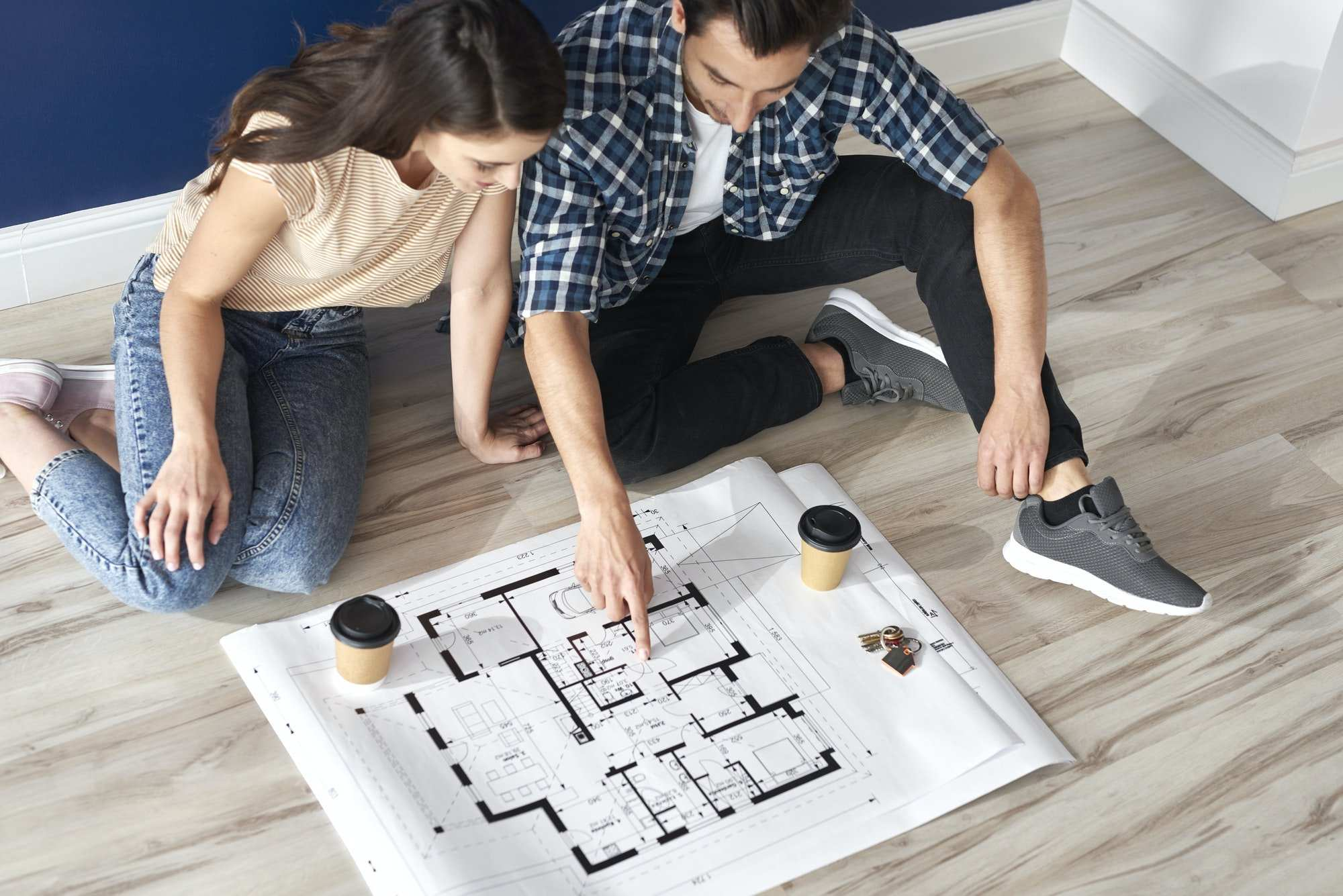 Couple looking at blueprint of new custom home builder near me