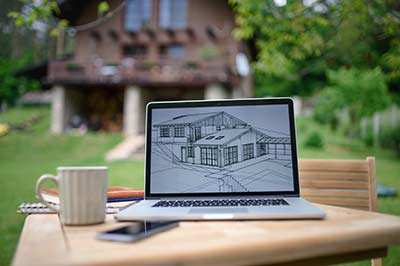 General contractor and new home construction blueprint on laptop in front of out of focus house.