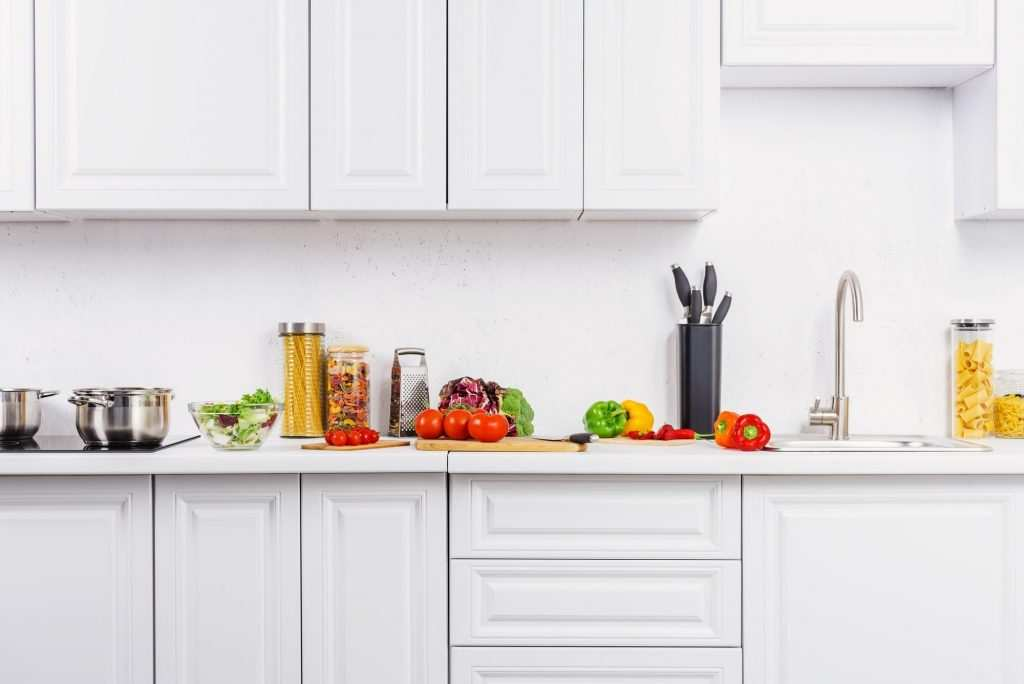 Best kitchen cabinets in Columbus, and throughout Central Ohio showing white doors and boxes with vegetables on quartz countertops